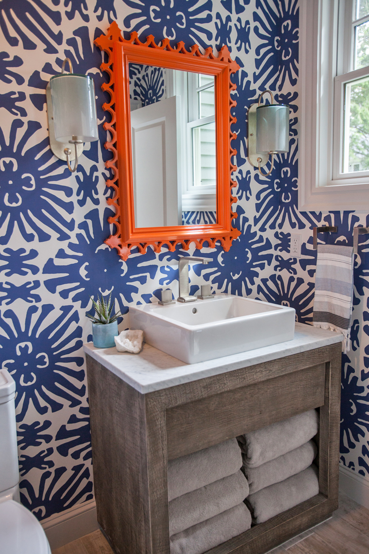 """Quadrille's """"Sigourney"""" wallpaper is a total showstopper in the pool house bath. Love the contrasting orange from the fab Oomph mirror!"""